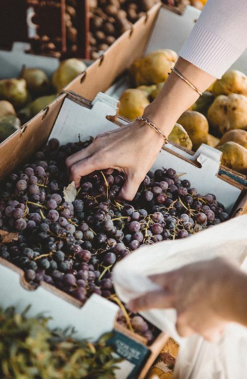 Hand greift in Karton, der mit Trauben gefüllt ist
