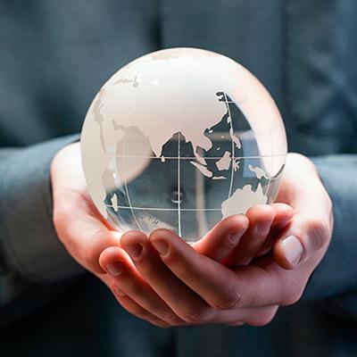Glas-Kugel in Form der Erde in einer Hand