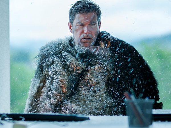 Ein Mann sitzt in einem Büro, in dem es schneit
